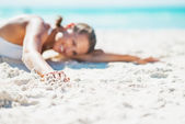 Closeup on young woman in swimsuit laying on beach — Stock Photo