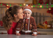 Portrait of mother and baby in christmas decorated kitchen — Stock Photo