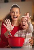 Closeup on mother and baby hands smeared in flour — Stock Photo