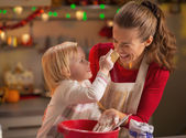 Baby trying to smear mothers nose with flour — Stock Photo