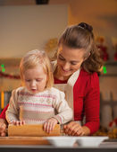 Mother and baby rolling pin dough in christmas decorated kitchen — Stock Photo