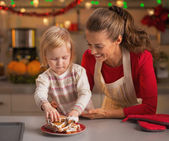 Baby taking homemade christmas cookies from plate — Stock Photo
