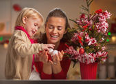 Happy baby helping mother decorate christmas tree — Stock Photo