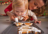 Baby helping mother decorate homemade christmas cookies with glaze — Stock Photo