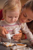 Mother and baby decorating homemade christmas cookies with glaze — Stock Photo