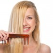 Happy young woman combing hair — Stock Photo #41012509
