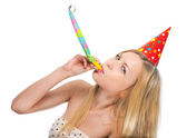 Young woman blowing into party horn blower — Stockfoto