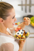 Happy young housewife eating fresh fruit salad — Stock Photo