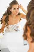 Concerned young woman checking facial skin condition — Stock Photo
