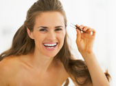 Happy young woman with tweezers — Stock Photo