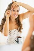 Happy young woman tweezing eyebrows — Stock Photo