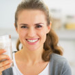 Portrait of happy young woman drinking smoothie in kitchen — Stock Photo #41056303