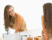 Smiling young woman sitting with wet hair in bathroom and lookin — Stock Photo