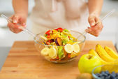 Closeup on young housewife making fruit salad — Stock Photo
