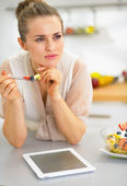 Young woman with tablet pc eating fruit salad — Stock Photo