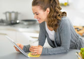 Happy young woman with smoothie using tablet pc in kitchen — Stock Photo