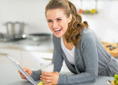 Smiling young woman with smoothie using tablet pc in kitchen — Photo