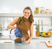 Happy young housewife pouring water into glass from water filter — Foto Stock