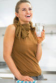 Happy young housewife with glass of water — Stock Photo