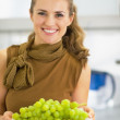 Happy young woman showing branch of grapes — Stock Photo