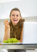 Happy young housewife with laptop eating grape in kitchen — Stock Photo