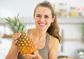 Happy young woman showing pineapple — Stock Photo