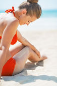 Happy young woman sitting on beach — Foto de Stock