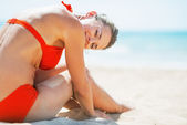 Relaxed young woman sitting on beach — Stock Photo