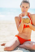 Happy young woman drinking coconut milk on beach — Stock Photo
