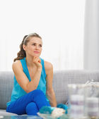 Thoughtful young woman sitting in living room — Stock Photo