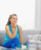 Pensativa jovem mulher sentada na sala — Foto Stock