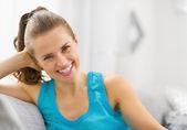 Leende ung kvinna sitter i vardagsrummet — Stockfoto