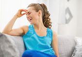年轻的女人坐在沙发上,笑着 — 图库照片