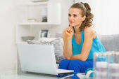 Thoughtful young woman sitting in living room and using laptop — Stock Photo