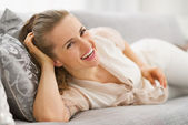 Portrait of smiling young housewife laying in living room — Stock Photo