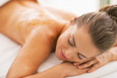 Young woman with honey on back laying on massage table — Stock Photo