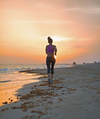 Fitness young woman running on beach in the evening — Stock fotografie