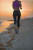 在晚上在海滩上跑步健身年轻女子的特写 — 图库照片
