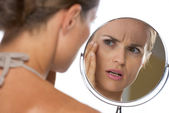 Concerned young woman looking in mirror — Stock Photo
