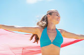 Happy young woman with parero rejoicing on beach — Stock Photo