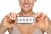 Closeup on young woman showing blistering package of pills — Stock Photo