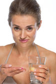 Doubting young woman with pill and glass of water — Stock Photo