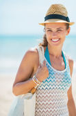 Portrait of smiling young woman in hat on beach — Stock Photo