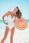 Portrait of happy young woman with hat on beach — Stockfoto
