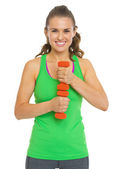 Portrait of smiling fitness young woman with dumbbells — Stock Photo