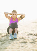 Fitness young woman doing abdominal crunch on beach — Stock Photo