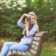 Young hipster taking photo with retro photo camera sitting on be — Stock Photo