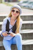 Hipster sitting on bench in the city — Stock Photo