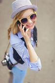 Hipster talking cell phone on city street — Stockfoto