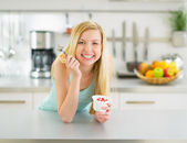 Woman eating yogurt in kitchen — Photo